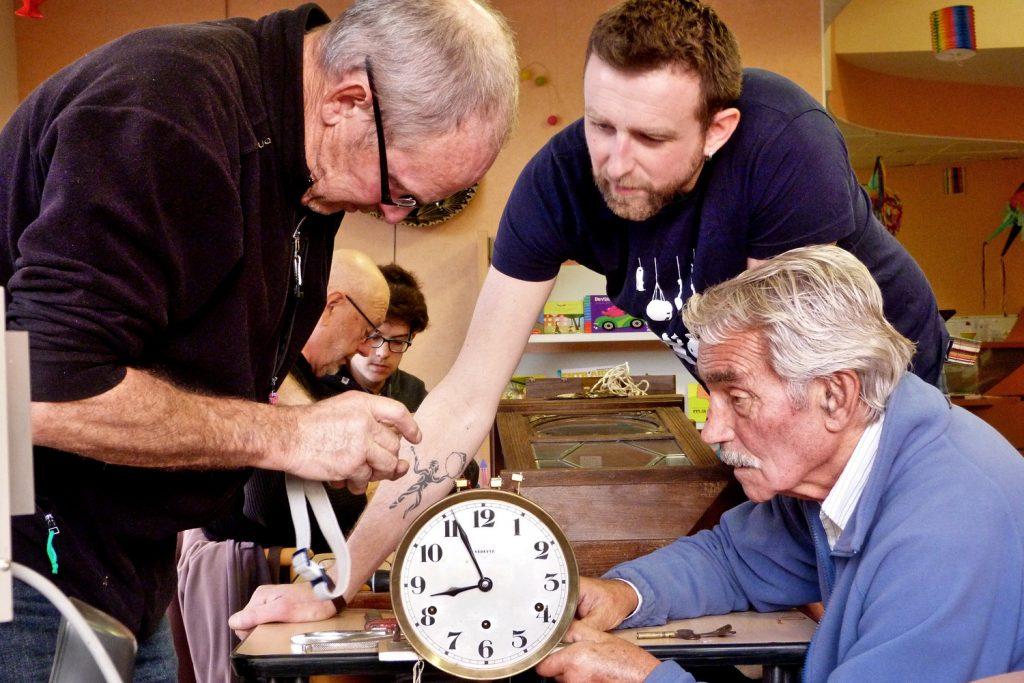 Les membres du collectif réparent une horloge